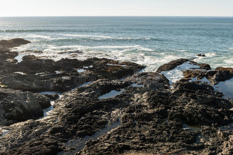 Waves crash on the rocks off the coast at Cape Perpetua Special Interest Area where Thor`s well is located stock image