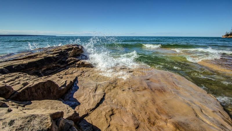 Waves Crash On The Rocky Coast Of Lake Superior. Waves crash on the rocky coast of the freshwater sea of Lake Superior on a beautiful sunny summer day with a royalty free stock photography