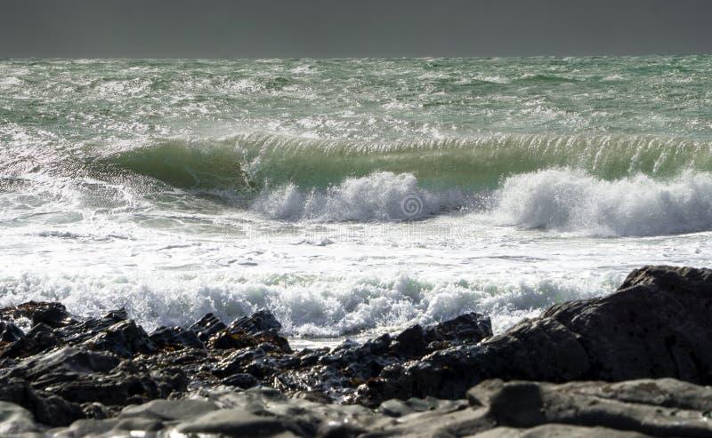 Waves crash on to the rocks and beaches of a cornish coastline,. UK royalty free stock photo