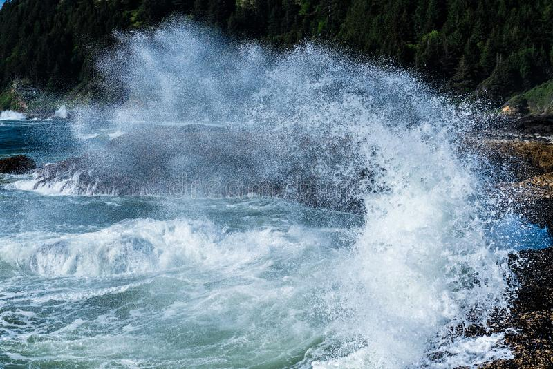 Wave frozen in crash against the rocky beach. royalty free stock photography