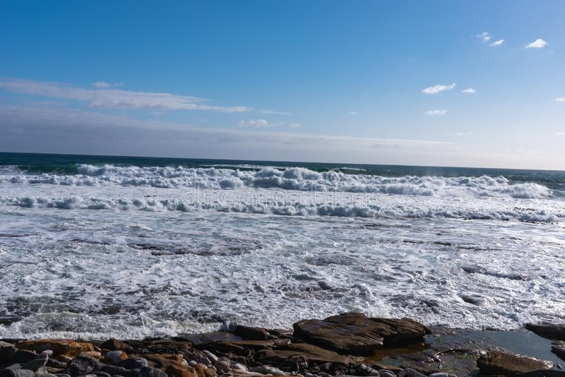 Waves crashing against a rocky shoreline. Waves crashing against a rocky shoreline in Kommetjie, Cape Town, South Africa stock photos
