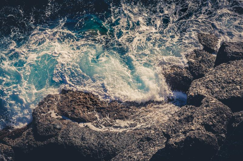Waves crashing breaking on the rocks. Drone aerial sea surface view royalty free stock image