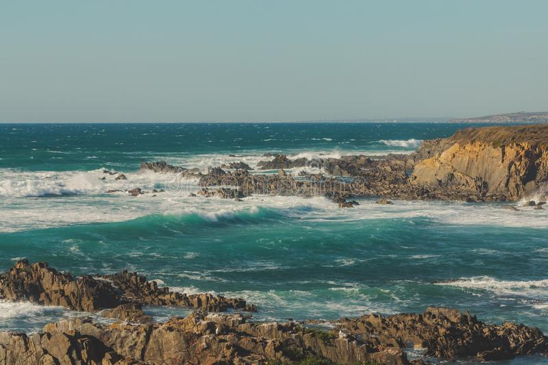 Waves crashing on the cliff and the rocks stock photography