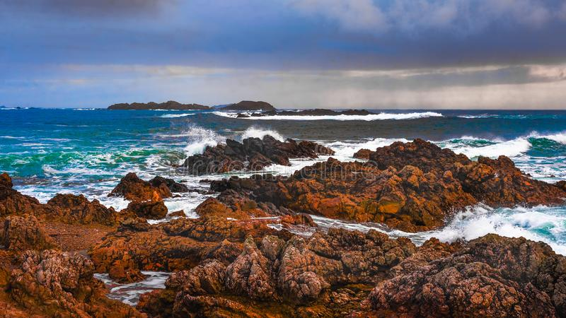 Waves crashing on Donegal coastline. Atlantic ocean waves crash onto the red rocks as rain falls in the distance. Part of the Wild Atlantic Way along the west royalty free stock images
