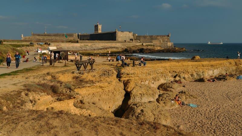Waves crashing near the 16th Century Saint Julian Fortress at Carcavelos beach near Lisbon, Portugal royalty free stock photos