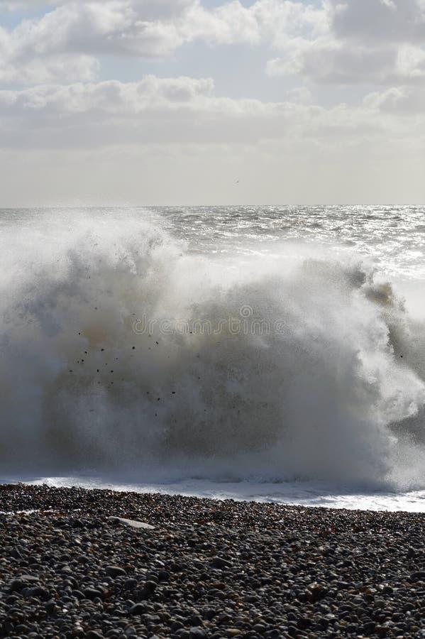Waves crashing onto pebble beach` stock photo