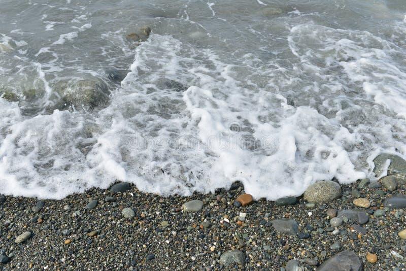 Waves crashing onto rocky shore stock photo