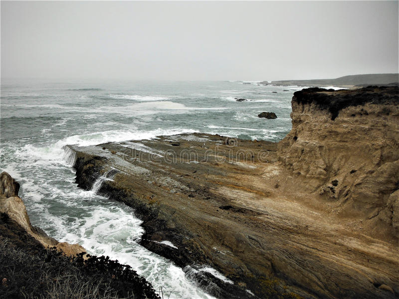 Waves Crashing Onto the Rocky Shoreline. On a foggy day at Montana de Oro State Park in Los Osos, California royalty free stock images