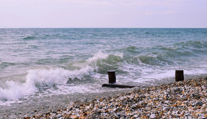 Ocean waves crashing onto a pebble beach. Waves crashing onto the shingle fossil beach at Bracklesham Bay West Sussex in the UK near East Wittering stock photography