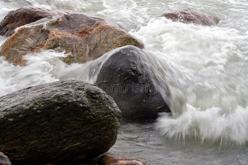 Waves Crashing over Granite Boulders at shoreline stock photography