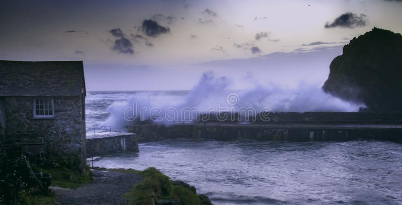 Stormy ocean waves break over harbour wall. Waves crashing over a harbour wall in Mullion Cove, Cornwall