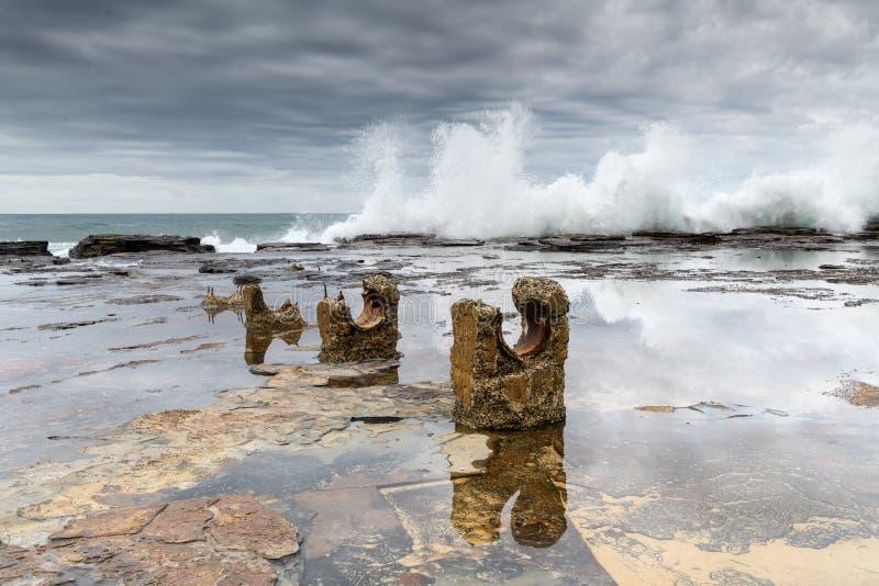 Waves crashing over the rock shelf at Coaldale beach near Sydney stock images