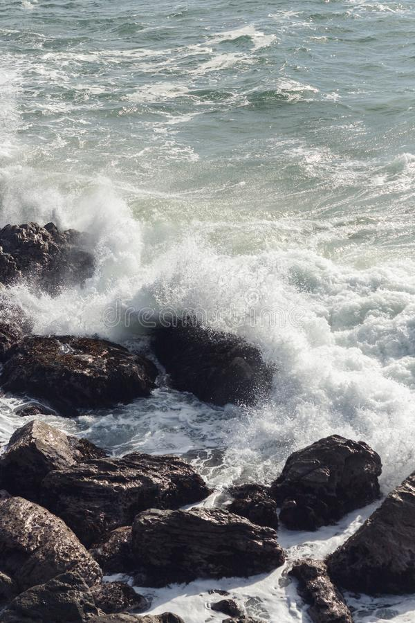 Waves crashing over rocks in NZ stock photography