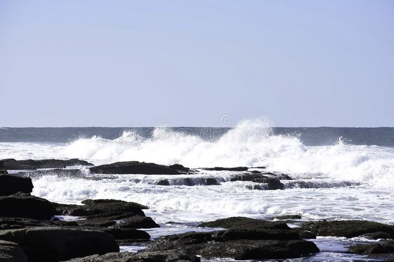 Waves Crashing Into Rock Pools As The Tide Comes In, Uvongo, South Africa. Waves crashing into rock pools as the tide comes in on a clear blue sky day at Uvongo royalty free stock images