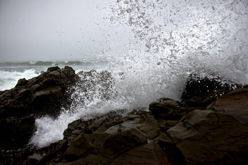 Waves crashing on rocks stock photo