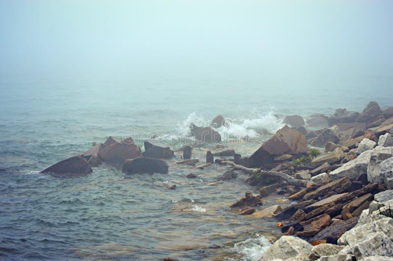 Waves Crashing Rocks Lake Michigan. Waves crashing up onto the rocks of Lake Michigan on a foggy, misty morning in Kenosha, Wisconsin royalty free stock photos