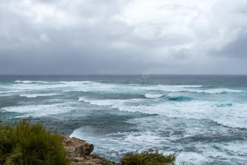 Waves crashing on the rocky coastline with dark ominous clouds. Waves crashing on the rocky coastline with dark ominous storm clouds building on the horizon stock photos