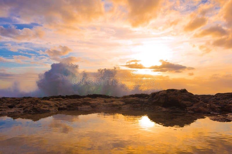 Waves crashing on rocky shoreline. During sunset golden hour royalty free stock images