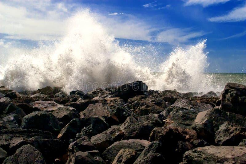 Waves crashing on the shore stock images