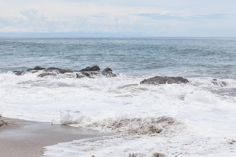 Waves crashing to rocks montezuma beach stock image