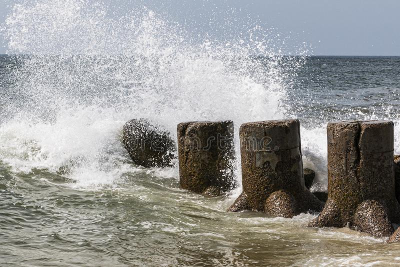 Waves crashing on to stone jetty. Atlantic Ocean waves croshing on to a jetty sticking out in to the water from the beach on the Fire Island National Sea Shore royalty free stock images