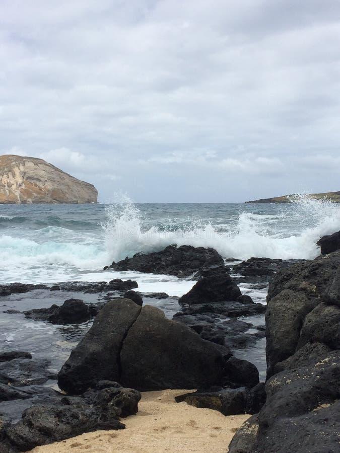 Waves crashing on volcanic rocks stock image