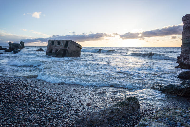 Waves crushing over rocks in sunset. Waves crushing over rocks and ruins of old fort at sunset on the beach royalty free stock images