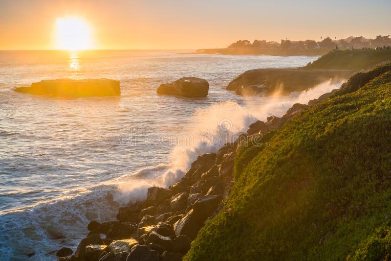 Waves crushing on the rocky shoreline at sunset, Santa Cruz, California. Bright sky at the horizon in the background stock image