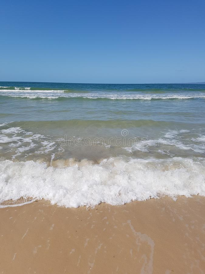 Waves froth on the shore of bribie island royalty free stock photo