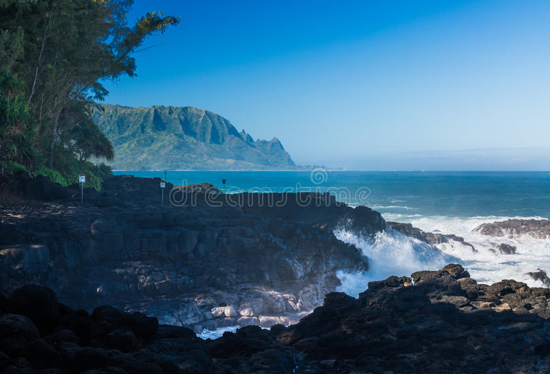 Waves hit rocks at Queens Bath Kauai. Waves crash into narrow gully by Queens Bath Princeville, Kauai, Hawaii royalty free stock images