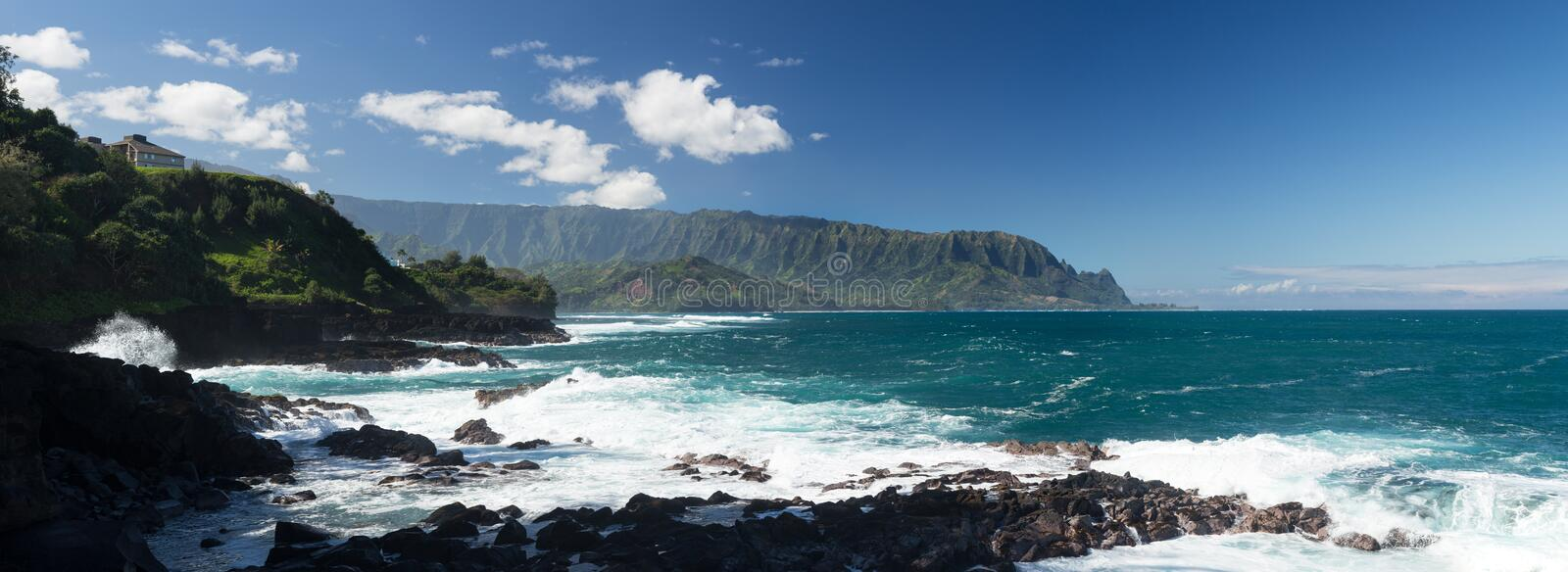 Waves hit rocks at Queens Bath Kauai. Panoramic view of Hanalei Bay and Na Pali mountains as waves crash against shore near Queens Bath at Princeville, Kauai royalty free stock image