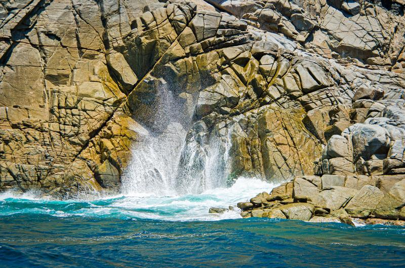 Waves hitting the rock with turquoise blue water in Huatulco, Oaxaca, Mexico.  stock photo