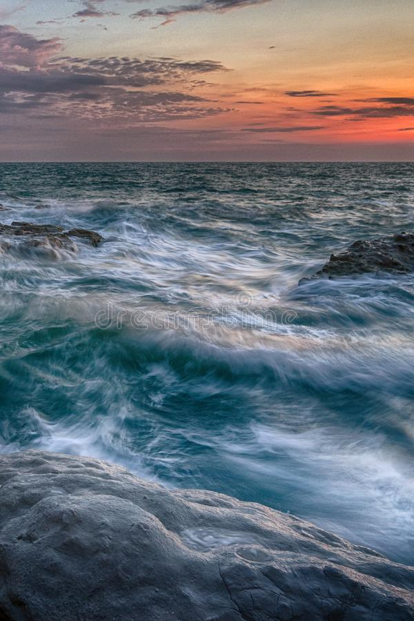 Waves hitting rocks at sunrise. Sea waves against the rocks at sunrise nature background or wallpaper royalty free stock photography