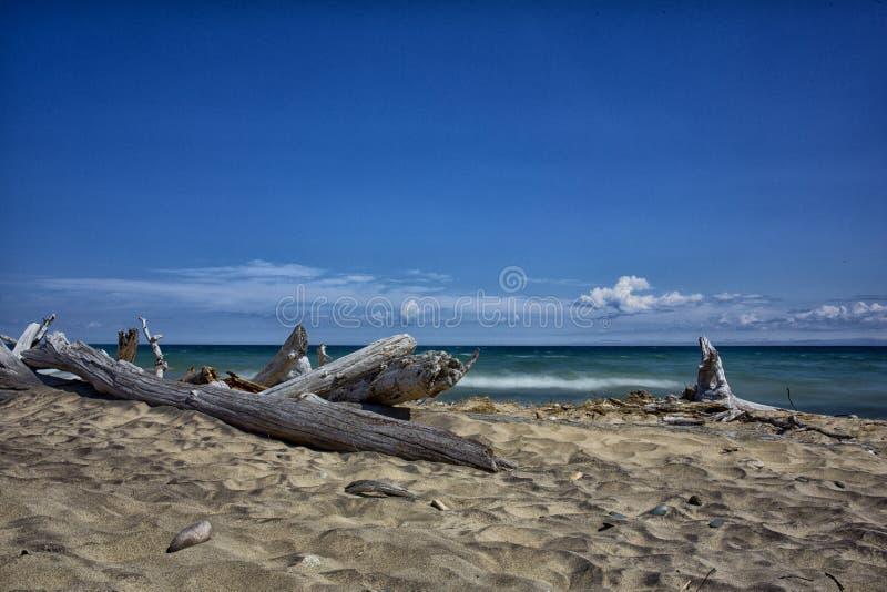 Waves kommer till en kust av sanden arkivfoton
