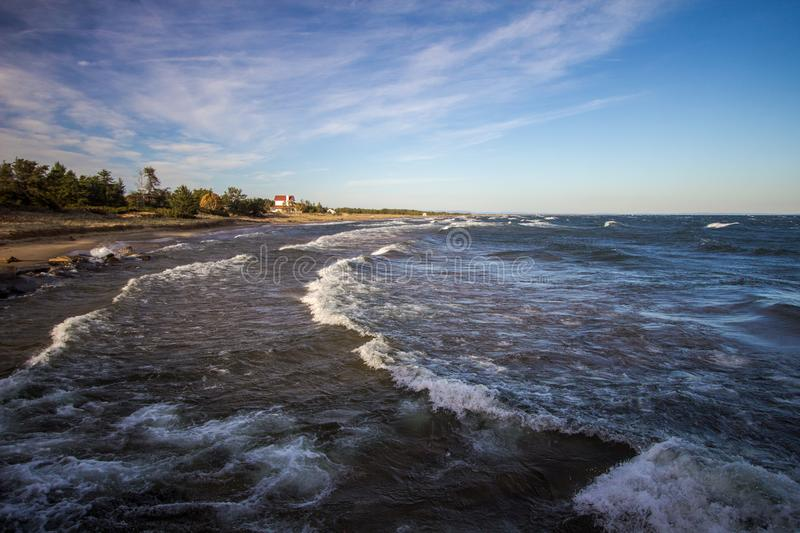 Waves On Lake Superior Coast In Michigan. Waves crash on a scenic coast of Lake Superior on a sunny summer blue sky afternoon in the Upper Peninsula of Michigan royalty free stock photo