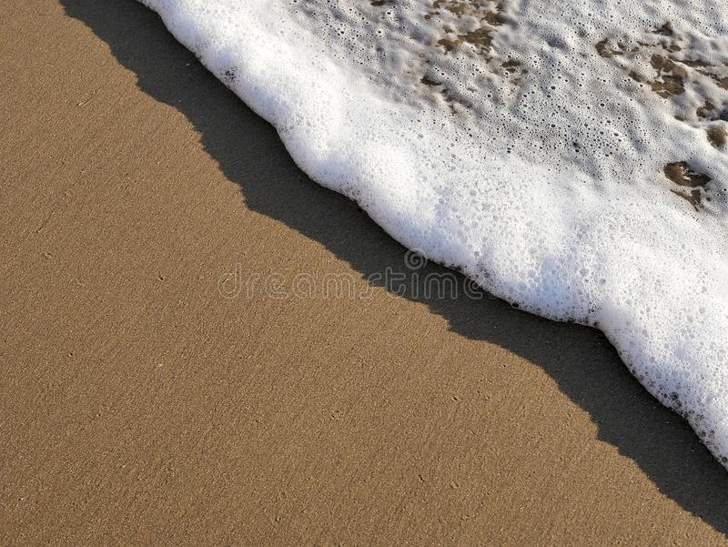 Waves lapping against sand on the California coast. Sea foam and sandy beaches in summer sunlight for travel blogs, website banner. S, social posts stock images