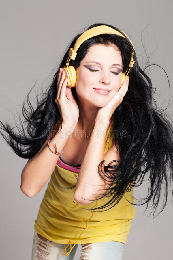 Waves of music. Girl with uncurled hair and headphones royalty free stock photography