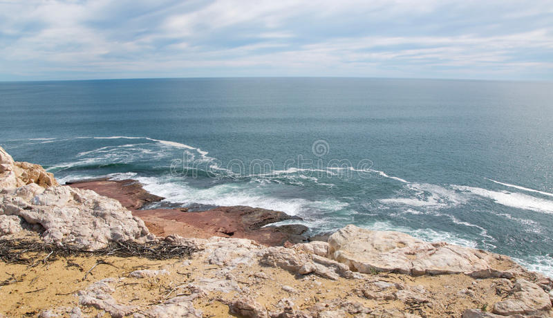 Waves at Red Bluff. Scenic view from the cliffs at Red Bluff beach of the turquoise Indian Ocean seascape with red sandstone rock under an overcast sky on the stock photos