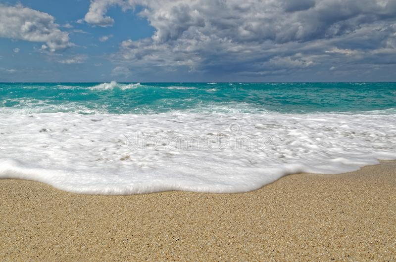 Waves on the Riaci beach, Tropea, Italy. Turquoise water and cloudy sky on the Riaci beach near Tropea, Italy royalty free stock images