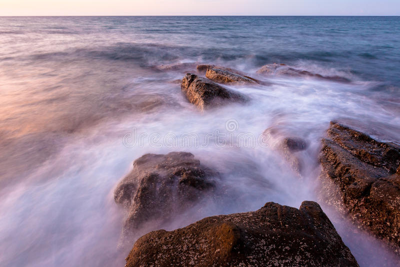 Waves and rocks shore long exposure royalty free stock images