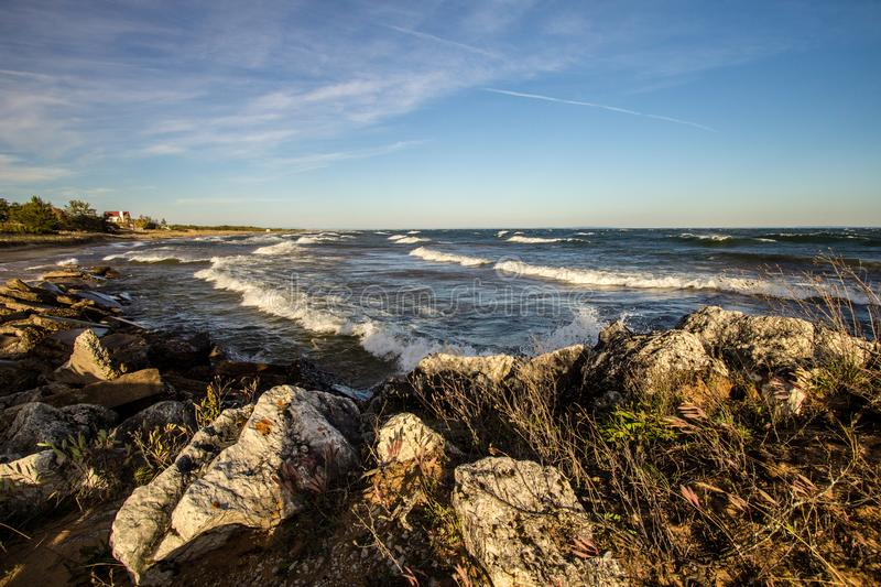 Waves On The Rocky Sea Coast Of Lake Superior. Waves crash on the rocky coast of Lake Superior on a sunny summer afternoon on Whitefish Bay in the Upper royalty free stock photos
