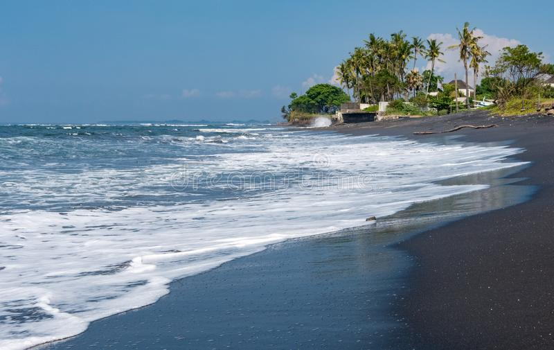 Black sands of Pabean Beach in Bali. Waves roll up the black sands of Pabean Beach in Bali, Indonesia stock image