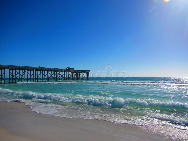 Waves rolling into a beach near fishing pier stock photography