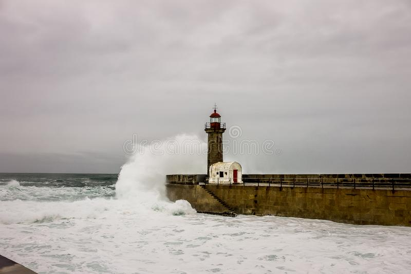 Waves of the sea breaking against the lighthouse of Oporto stock photos