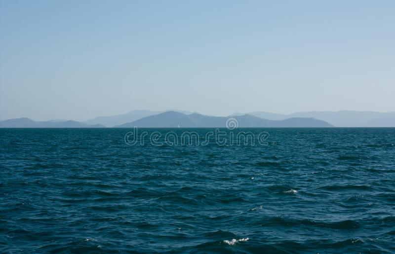 Waves, the sea and some islands in the distance in the Whitsundays in Australia stock image