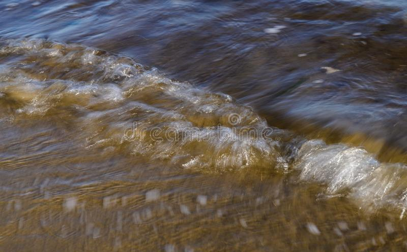 Waves on the seashore. Natural abstract motion background. Waves on the seashore captured with a slow shutter speed. Natural abstract motion background royalty free stock images