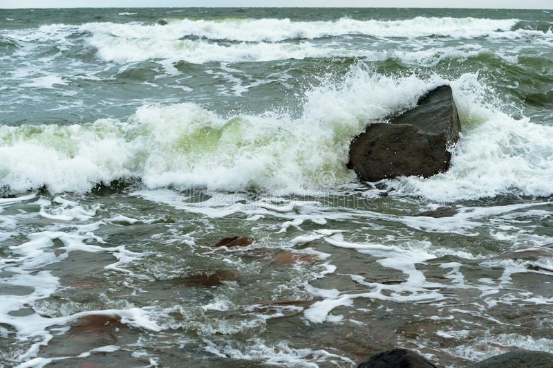 The waves splash on the shore, the waves beat against the rocks stock photo