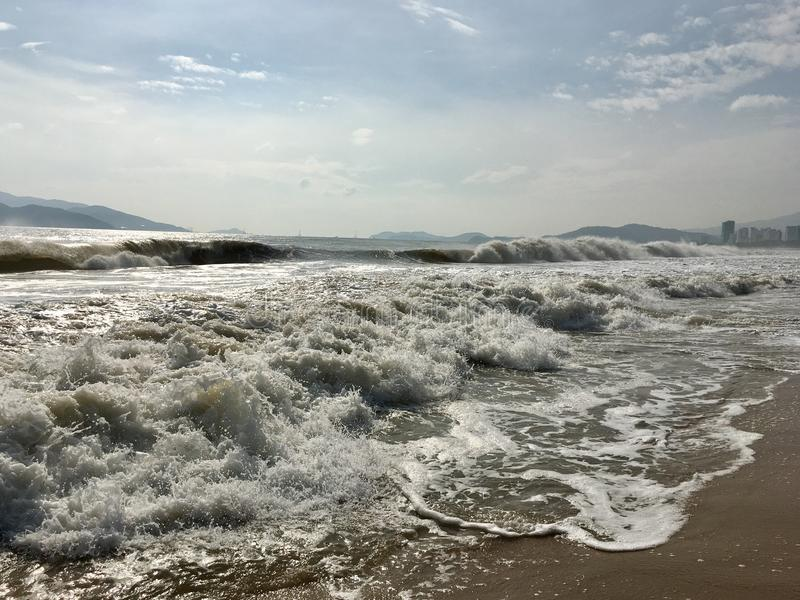 Waves splashing on the beach. In the morning, the rays of the sun glisten on the sea water, wave after wave runs ashore, on the horizon of low mountains, sky stock image