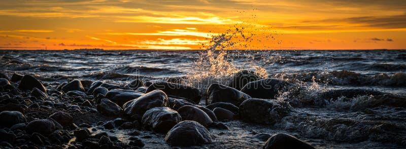 Waves Splashing at Stones on Beach during Sunset stock photo