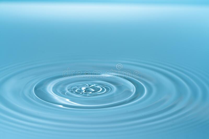 Waves on the surface of the water from a collision. Drop of water drop to the surface royalty free stock image